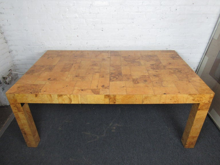 Vintage dining room table by Paul Evans in a rich golden shade of burlwood. The table's intricate woodgrain is sure to catch eyes and allow this piece to stand out as a unique and stylish centerpiece of any dining room. Three leafs allow for an