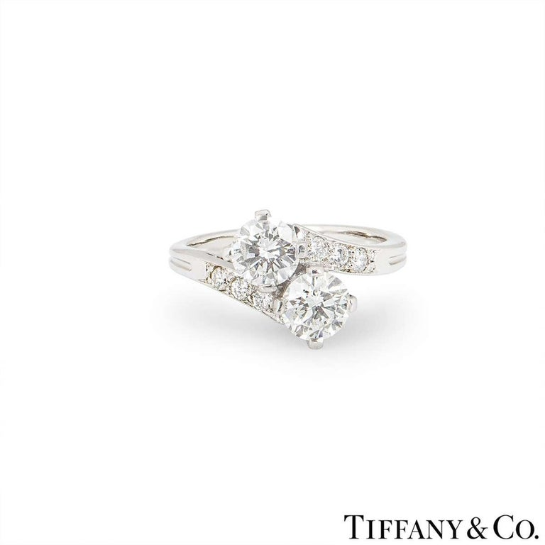 A diamond set ring in platinum by Tiffany & Co. The crossover design ring is set to the centre with two round brilliant cut diamonds in a four claw setting, totalling approximately 1.00ct, H/I in colour and VS in clarity. Accentuating the central