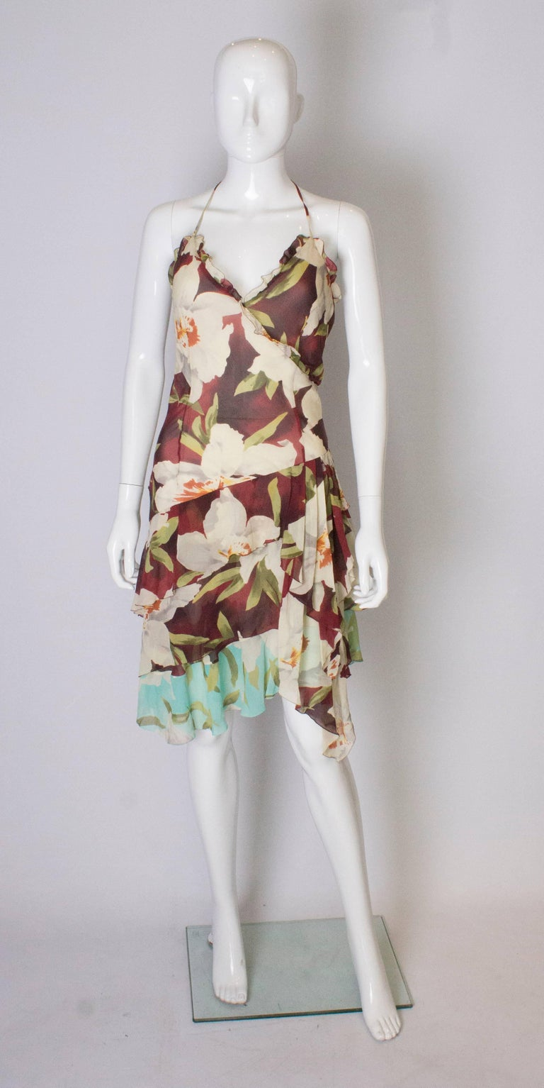 A 1990's pretty, floaty , floral silk dress by Cacharel. The dress is in a floral print with layers of silk,   and has spagetti straps and a hankerchief hem.  It has a side zip and is fully lined.