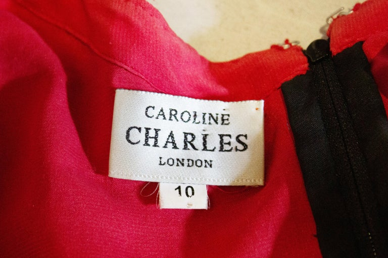 A stunning vintage evening top by Caroline Charles. The outer layer is in black lace with sequin and bead detail, and the lining layer is black and red. It has a sweetheart neckline and a v backline. with a zip opening and scalloped hem.