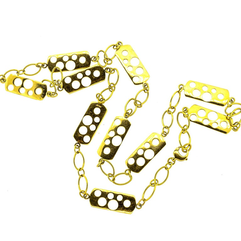 Unusual vintage Cartier 18k yellow gold fancy link necklace from the 1970s. This chain has panels of gold with cut out circles of different sizes and large loop links in between. The chain is light looking though it is hefty, and has nice dimension.