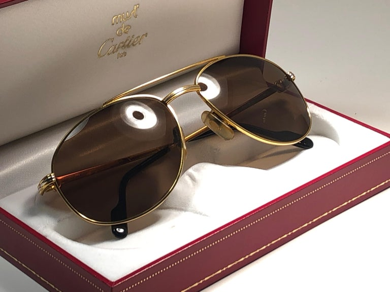 New condition 1990 Cartier Driver 60 [] 18 Sunglasses with brown (uv protection) lenses. All hallmarks. Cartier gold signs on the ear paddles. These are like a pair of jewels on your nose.  Please notice that this sunglasses are nearly 30 years old