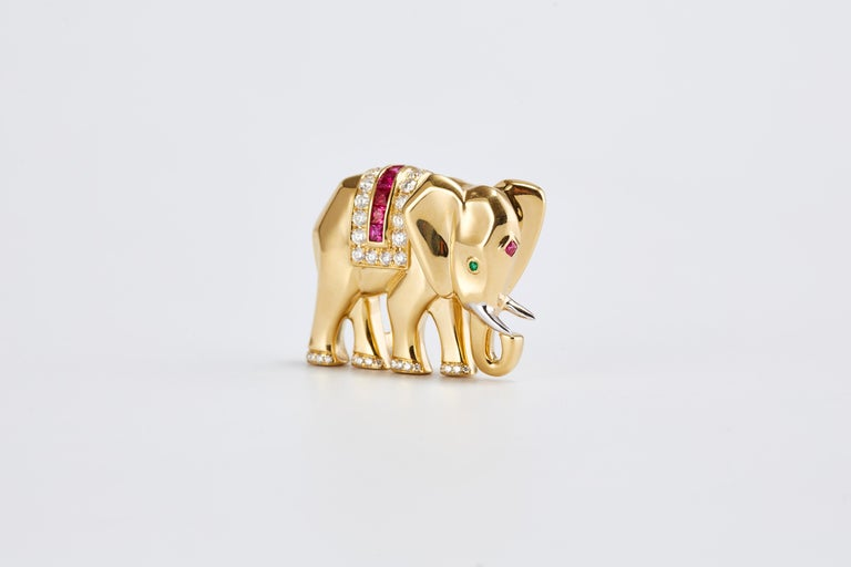 A vintage Cartier elephant pin/brooch in 18-karat yellow gold, with circular-cut emerald eye, and a ruby mark on the forehead.  Diamonds and ruby in the center of the pin and diamonds decorating the feet. Circa 1990s.  Total weight: 20.65 gr