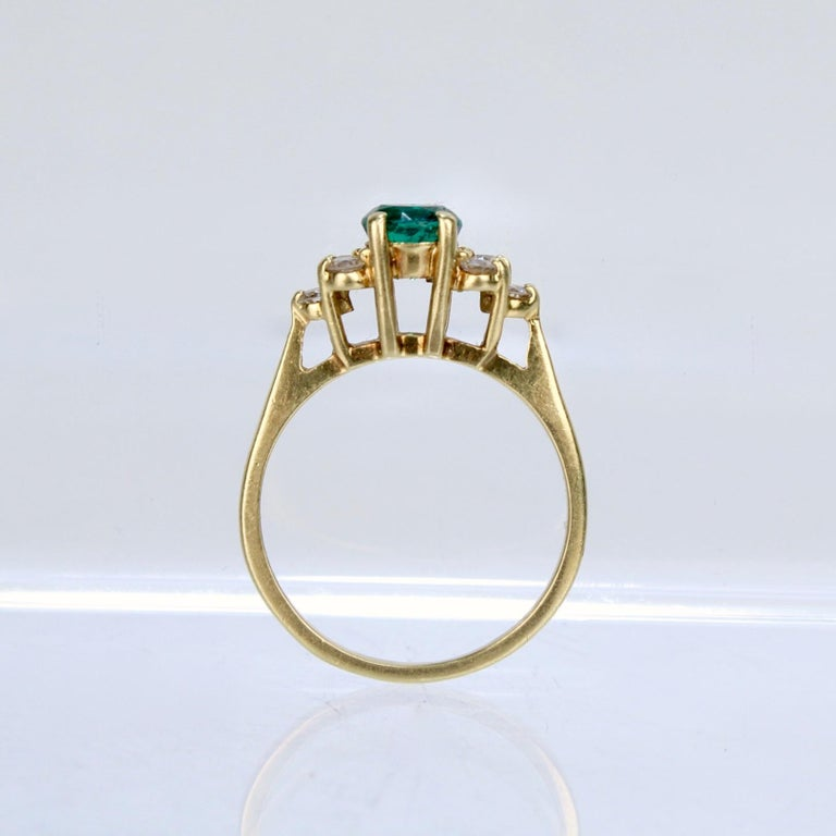 A wonderful 18k gold, diamond and emerald cocktail ring.  From the long-storied Cardow jewelers of the US Virgin Islands.  With a round-cut emerald set at its center and flanked on each side by a cluster of 3 white diamonds.   Each stone is prong