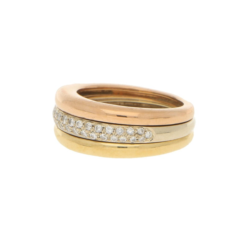 A beautiful pave set diamond ring in 18-karat tricolour gold, signed Cartier; circa 1990. This piece is cleverly designed to move with the finger as the three bombe like bands partially rotate.  The central band is pave set with 34 round
