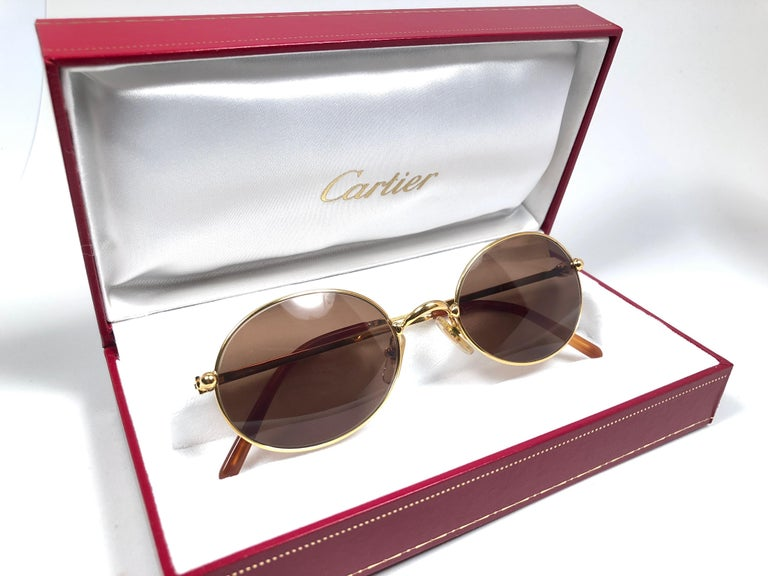 1990 Cartier Saturne Sunglasses with brown (uv protection) lenses. All hallmarks. Cartier gold signs on the ear paddles.  These are like a pair of jewels on your nose.  Please notice this pair is nearly 30 years old and may have minor sign of