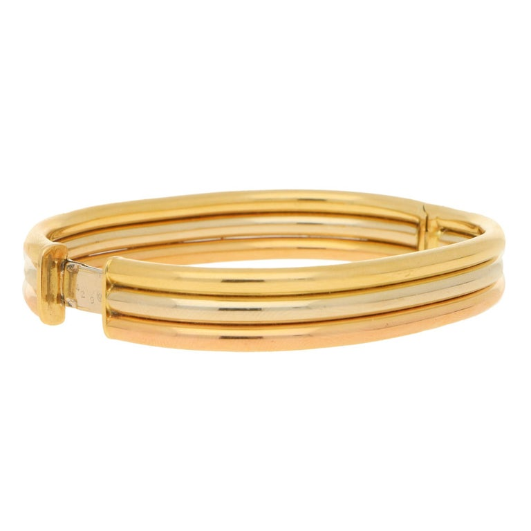 A classic vintage Cartier trinity bangle crafted in 18k yellow, rose and white gold. Because the bracelet is designed to be solid instead of the typical trinity design, once on, we see these lovely grooves in the bracelet which has a beautiful