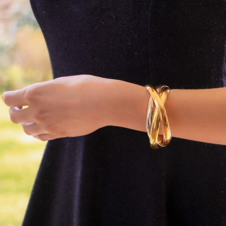 A classic vintage Cartier Trinity bangle set in 18k yellow, rose and white gold, circa 2000.  The bracelet is composed of three interlinked 8.5-millimetre bangles that are designed to roll with ease on the wrist. The trinity bangles come in three