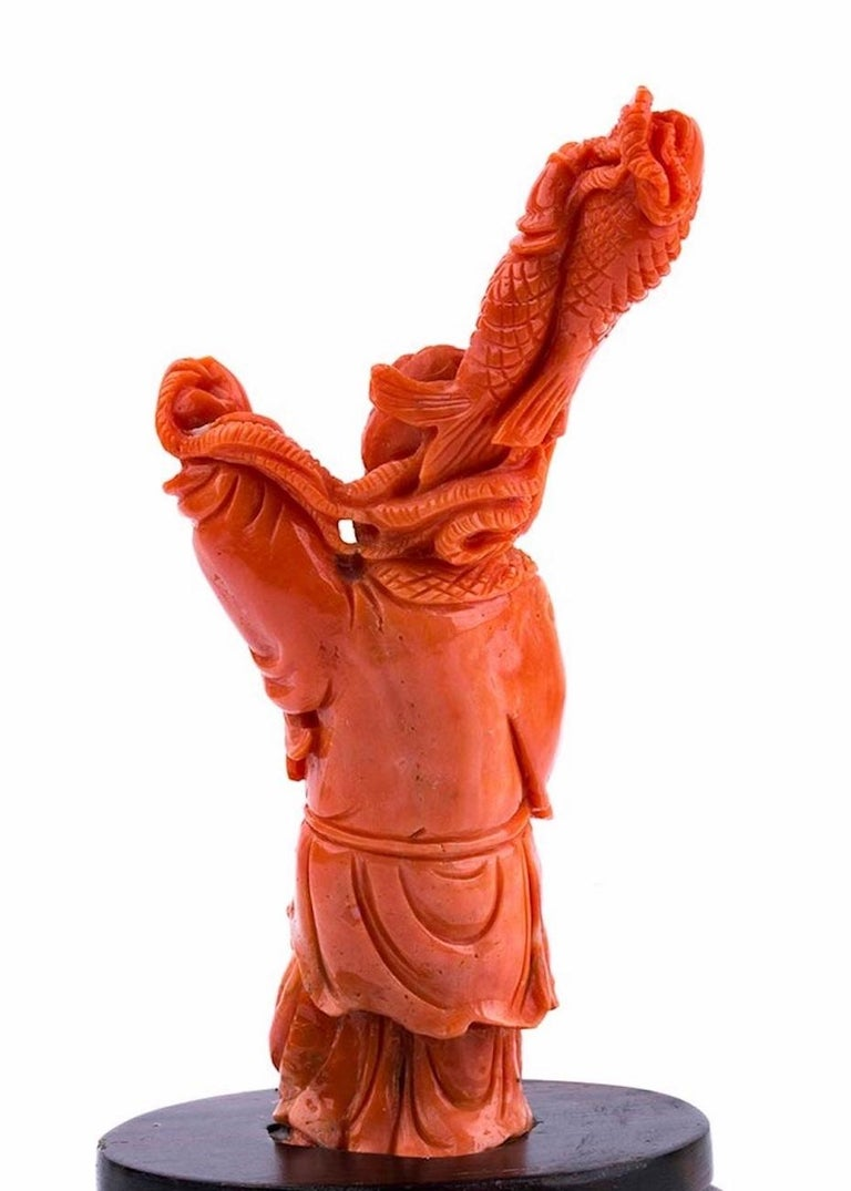 This is a splendid Carved Coral depicting the god Ebisu, realized in Japan in the early 20th century. You may see a Japanese coral (C. Japonicum) carving standing on a wooden base.  Ebisu is one of the most revered deities in Japan, he is the god