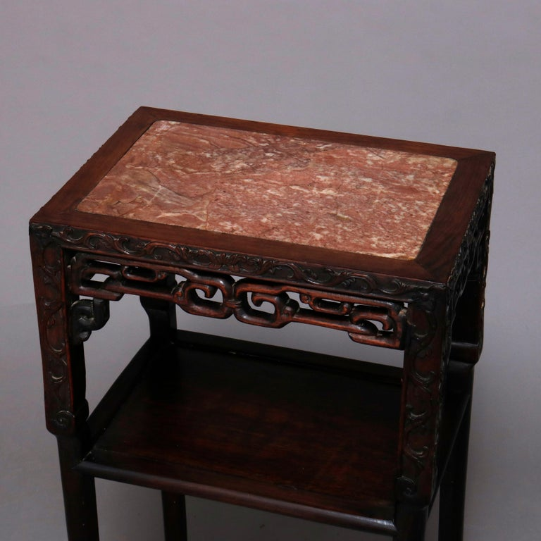 A vintage Chinese plant or side stand offers inset marble top seated in carved hardwood frame having pierced skirt and lower display shelf, 20th century.  ***DELIVERY NOTICE – Due to COVID-19 we have employed LIMITED-TO-NO-CONTACT PRACTICES in the