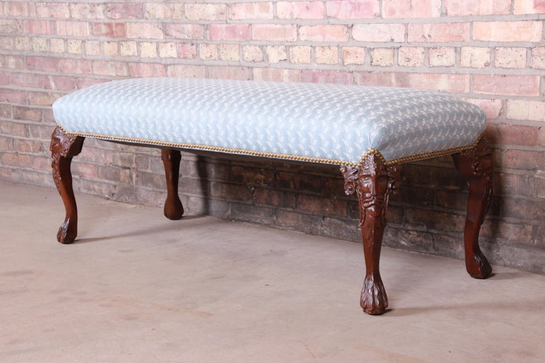 A gorgeous vintage carved mahogany upholstered window bench or bed bench,  20th century.  Mahogany cabriole legs with carved faces, and studded light blue and ivory upholstery.  Measures: 51.88