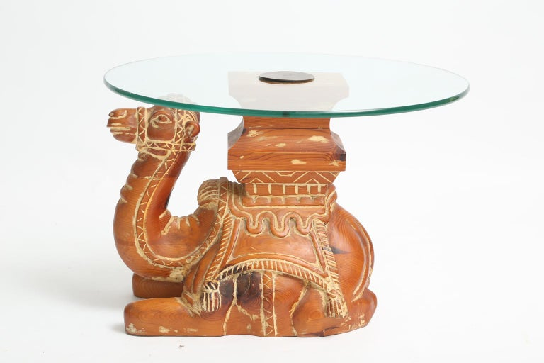 Accent table, having a round top of glass, on base of pine, carved as a well-articulated camel in recumbent pose.   Stock ID: D2252
