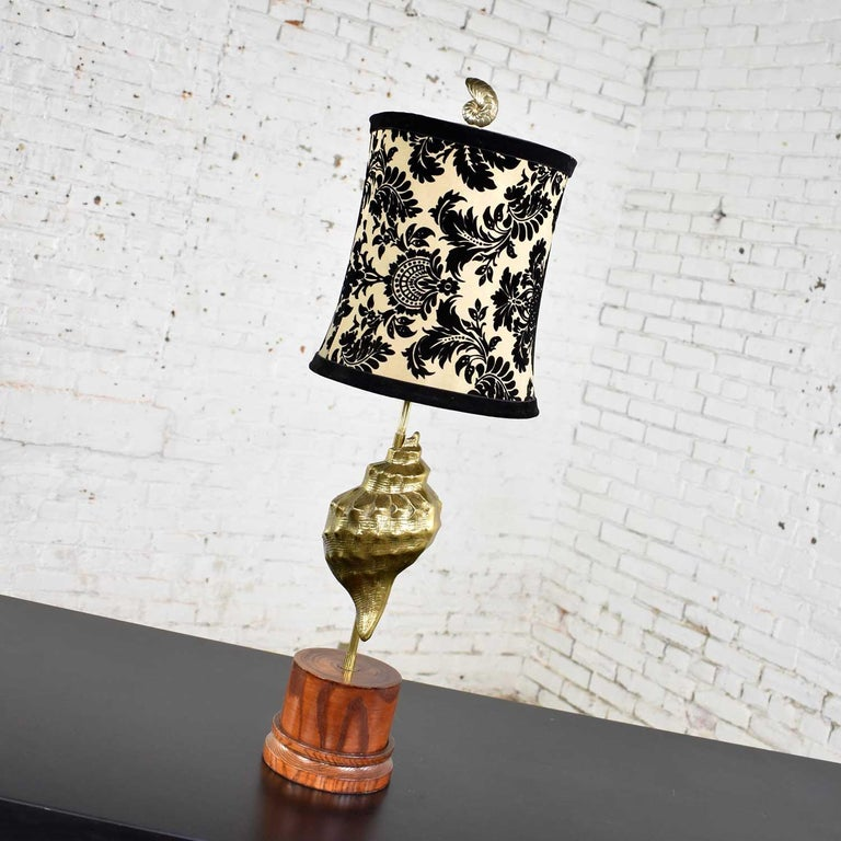 Awesome vintage cast brass conch shell table lamp on a turned wood base. It is adorned with a relatively new black velvet and taffeta lamp shade. It is in wonderful vintage condition with age appropriate wear to both lamp and shade. Please see