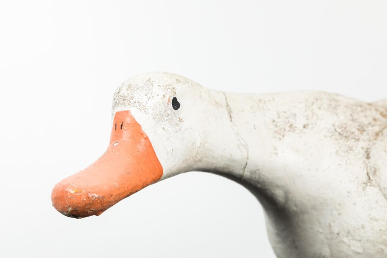 Vintage concrete and garden duck with cast iron feet. Old original paint surface.