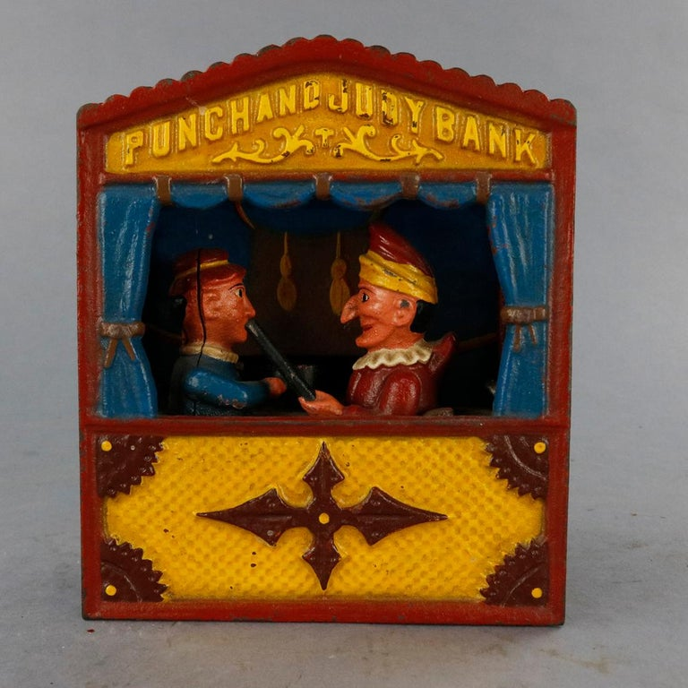 A vintage book of knowledge Punch & Judy mechanical bank offers polychrome cast construction with puppet stage and figures with embossed title, underside reads