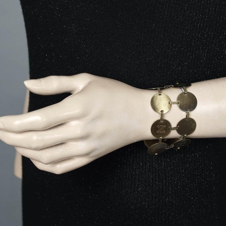 Vintage CELINE Blazon Logo Disc Coin Link Bracelet  Measurements: Height: 1.77 inches (4.5 cm) Wearable Length: 6.69 inches (17 cms)  Features: - 100% Authentic CELINE. - Two tiered coin/ disc bracelet with CELINE blazon logo. - Old bronze tone