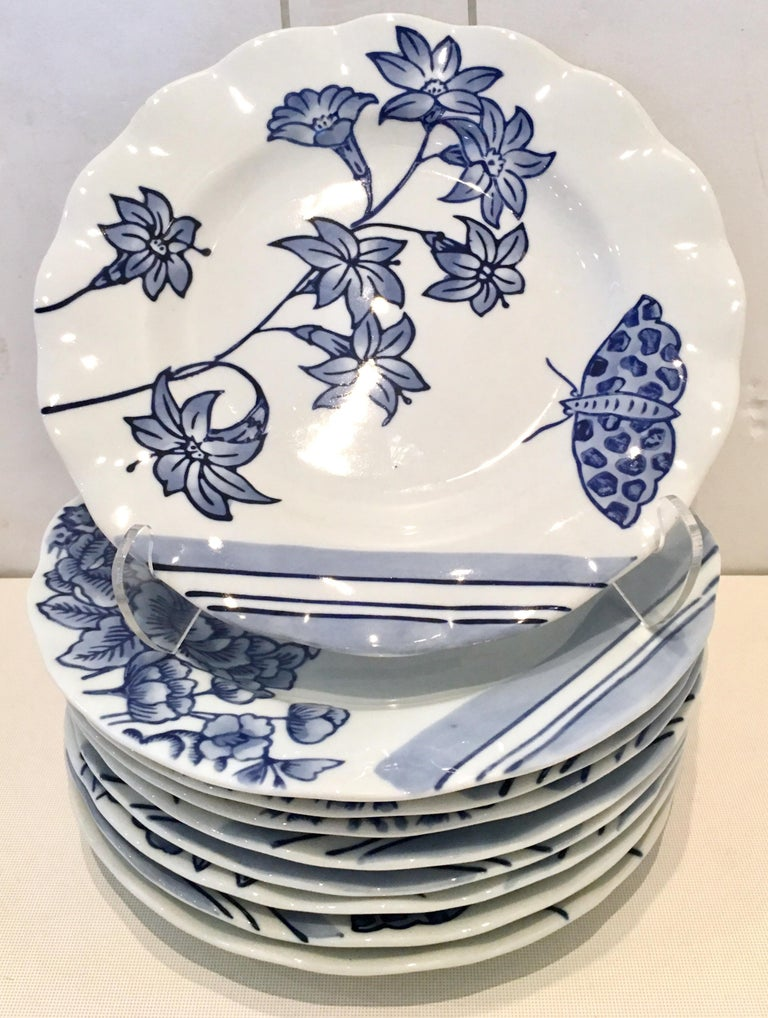 20th century ceramic salad/dessert plates, set of nine pieces by, Creativeco-op. Pattern features a bright white ground with ink blue floral pattern. There are three each of different motifs, bird, butterfly and dragonfly. with a scalloped edge.