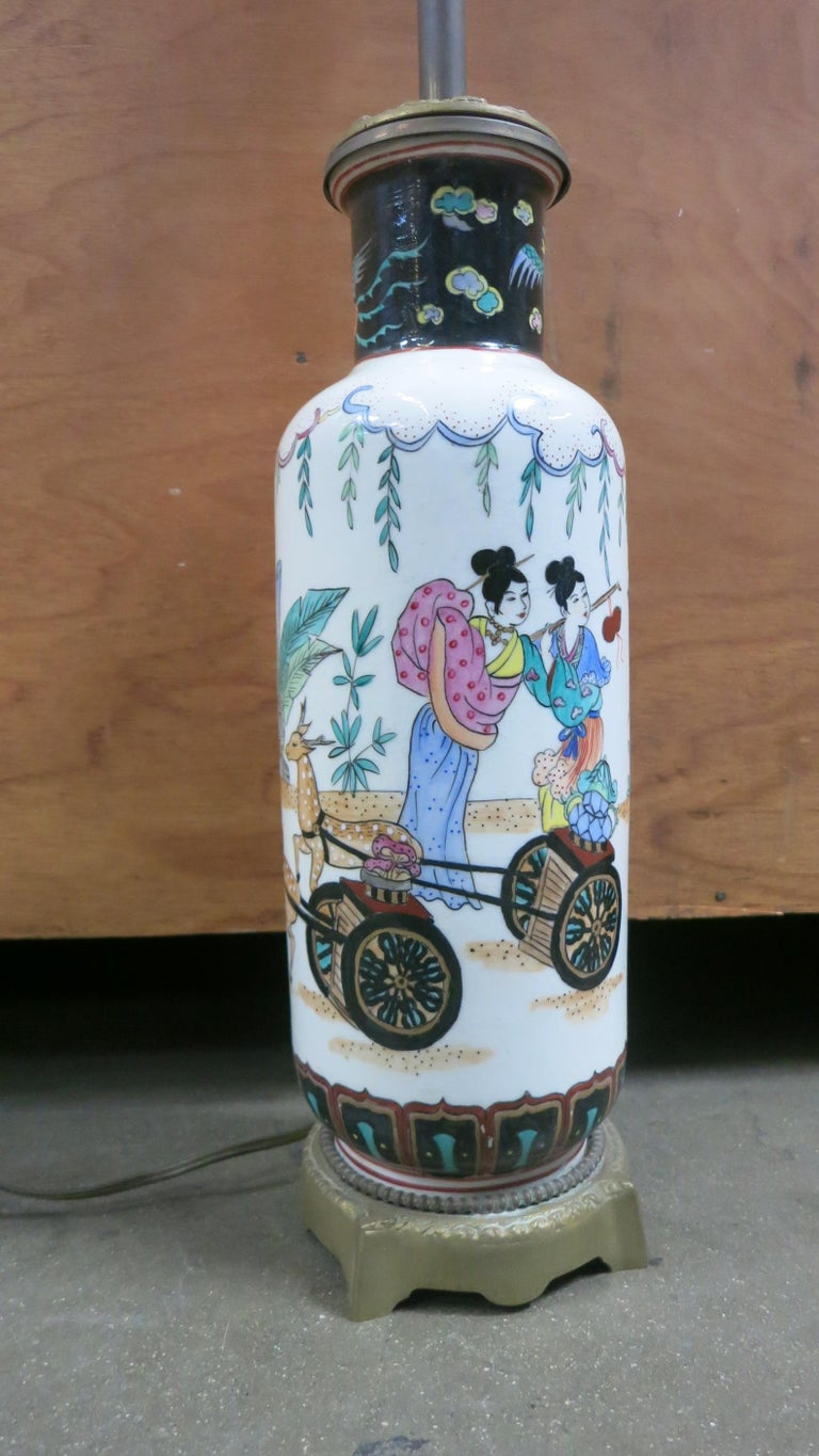 Mid Century table lamp, shaped like an Asian vase. White ceramic with painted scenes of Geishas. The top and bottom are metal. This piece is in excellent condition and functions perfectly.  Dimensions: 28