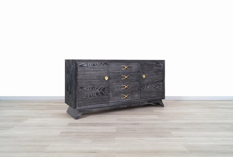 Wonderful vintage cerused and brass credenza designed by Paul Frankl for Brown Saltman in the United States, circa 1950s. The beautiful black cerused oak grain gives it a unique style that makes it stand out even more from the rest. It has 2 doors