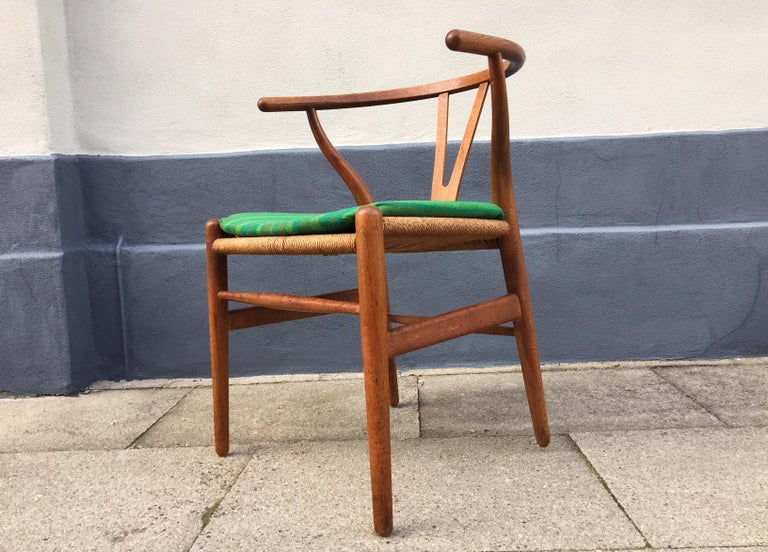 The CH24, Wishbone or Y-Chair was designed by Danish architect Hans Jørgen Wegner in 1949. This model was fashioned out of oak and manufactured by Carl Hansen & Søn in Denmark during the 1960s. The green period seat-cushion is included. The chair