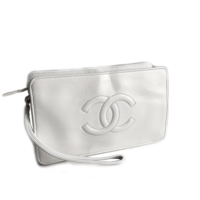 Authentic, preowned, vintage Chanel white leather CC logo clutch bag or wristlet, from the 90s. Matelasse quilting on one side/stitched CC logo on the other. Interior lined w/1 flat zip pocket. Gold metal hardware. Preowned/vintage w/minimal signs