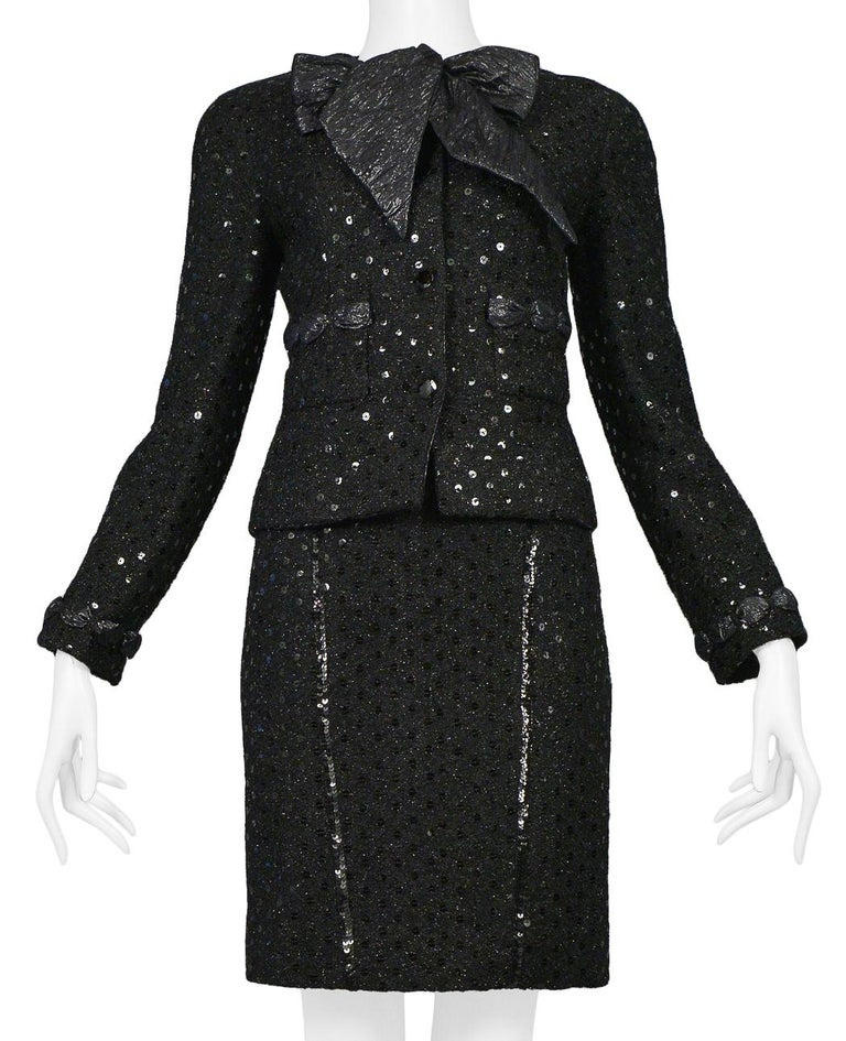 Vintage Chanel black boucle skirt suit ensemble. Jacket is embellished with sequins and woven taffeta ribbon detail. Quilted black taffeta crossback tank is paired with high waisted boucle skirt w/ black sequin detail throughout. This ensemble is a