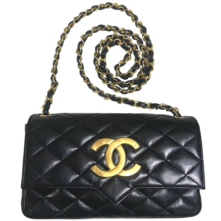 vintage CHANEL black lambskin shoulder bag with golden large CC logo motif.