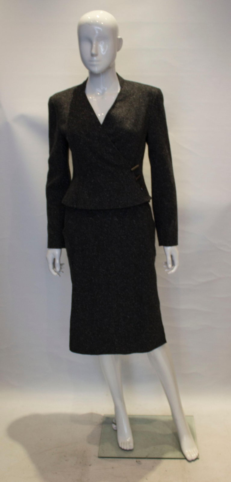 A charming and slightly unusual skirt suit by Chanel. The jacket is 100 % cashmere and lined in silk. It has a cross over v neckline and fastens with buttons and clips stamped Chanel.  The skirt is 100 % cashmere and unlined. It has a central back