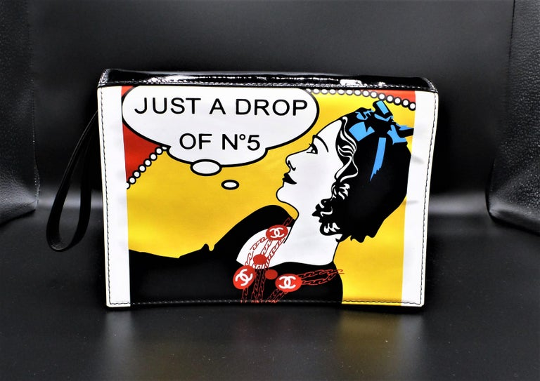 A very original clutch made of black patent leather, lined inside with black leather and has a side pocket. COCO CHANEL is shown on the front, it is a Vinyl hologram 'JUST A DROP OF NR. 5' The clutch has a handle on the side.  Measurement:  Width 22