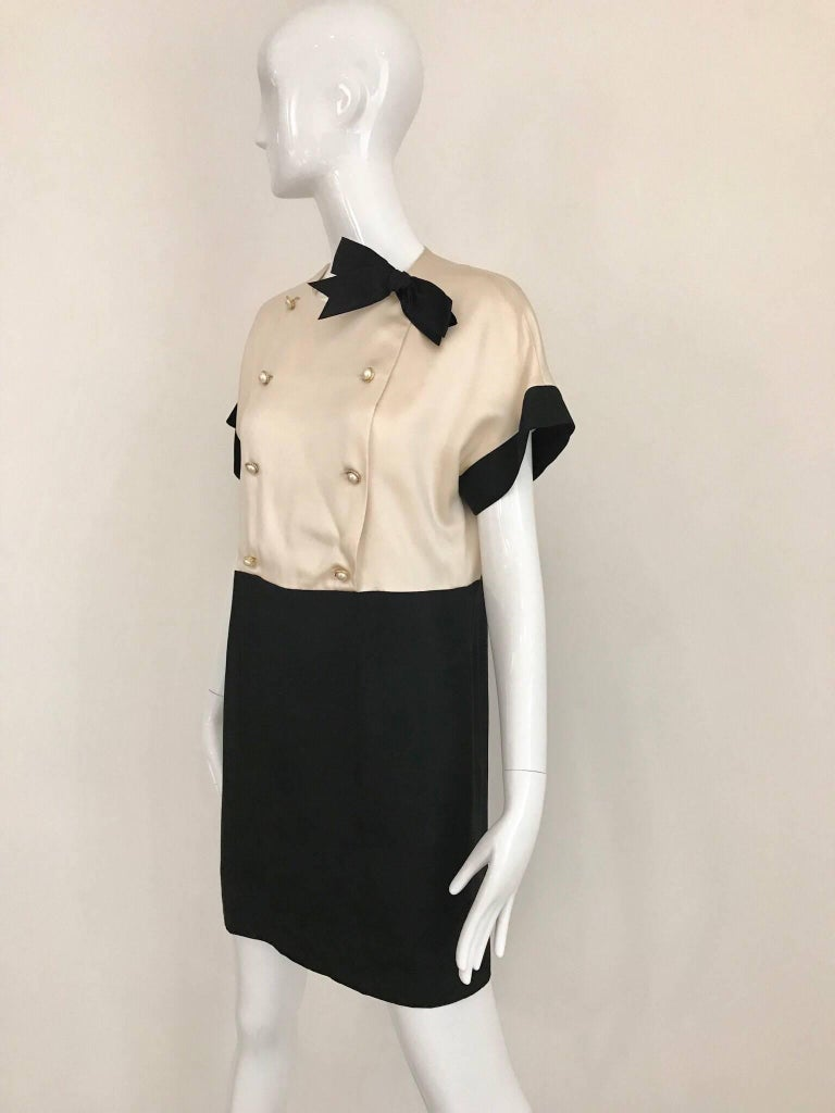 1980s Classic CHANEL Creme and Black silk charmeuse cocktail dress. Dress has gold pearl buttons and black satin bow.  Size: Small - Medium. 2/4/6 Bust: 39