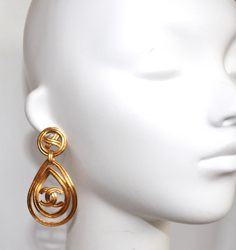 From the 1996 Spring Collection, double teardrop with CC and crisscross on clip.Signature logo on bottom of loop. gilded brass.