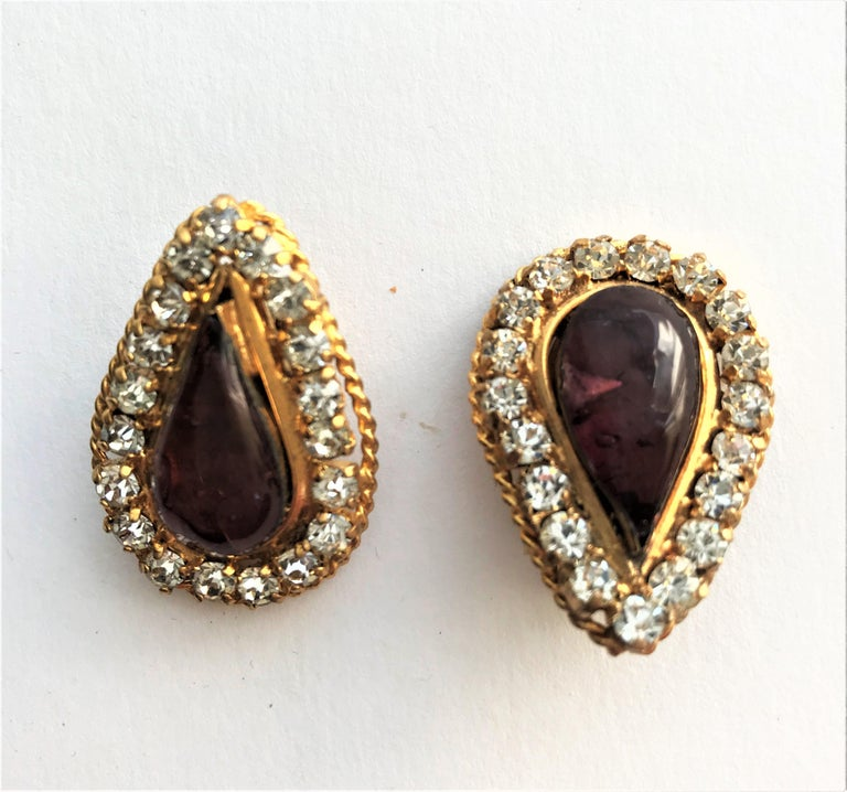 Very early Chanel ear clip from the 1970/80 in the shape of a teardrop. Transparent light purple Gripoix glass tropics bordered with small cut rhinestones. Edged with a fine gold-plated cord.  The crystals  are all set and not glued . Measurement.