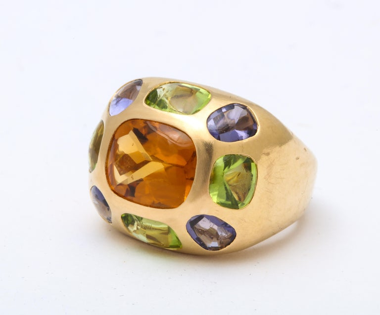 This fabulous vintage Chanel ring  has a  citrine center stone with smallwe semi precious peridot, citing and illiterate, all invisibly se,t in a classic mounting of 18 K gold.  It has authentic Chanel Paris hallmarks  and was  made in 1970