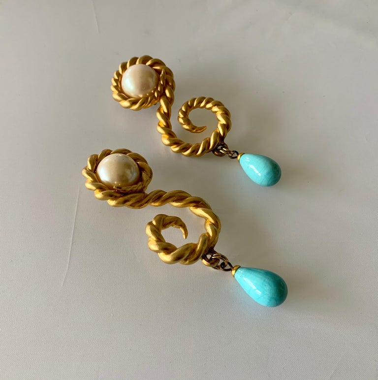 Scarce large vintage Coco Chanel statement clip-on earrings, comprised out of satin gold metal in a swirl motif, the earrings feature large pearls at the center and large turquoise