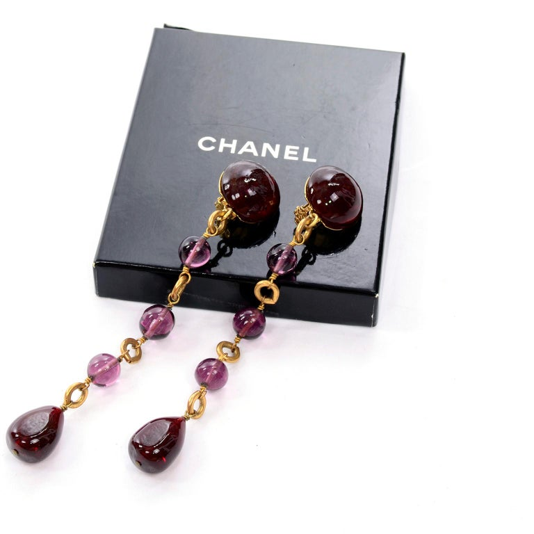 These are stunning vintage late 1980's or early 1990's Chanel clip earrings with purple gripoix stones on gold metal.  Marked Chanel made in France, these were designed during the years that Victoire de Castellane was overseeing the costume jewelry
