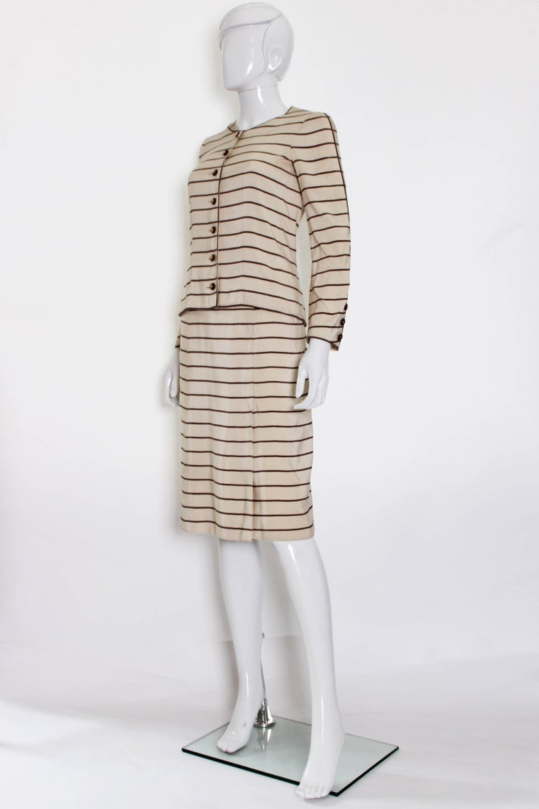 A charming and chic vintage (1974)  haute couture skirt suit by Chanel. The suit is made of a cotton/silk mix, taupe stripes on an ivory background. The suit is lined in silk , the buttons are made of wood, and the jacket has a chain in the hem. The