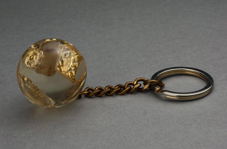 Vintage CHANEL Iconic Charm Lucite Ball Keychain  Measurements: Height: 4 4/8 inches (11.43 cm) Circumference: 4 4/8 inches (11.43 cm)  Features: - 100% Authentic CHANEL. - Lucite ball with iconic charms: 2.55 flap bag, turtle, camellia flower,