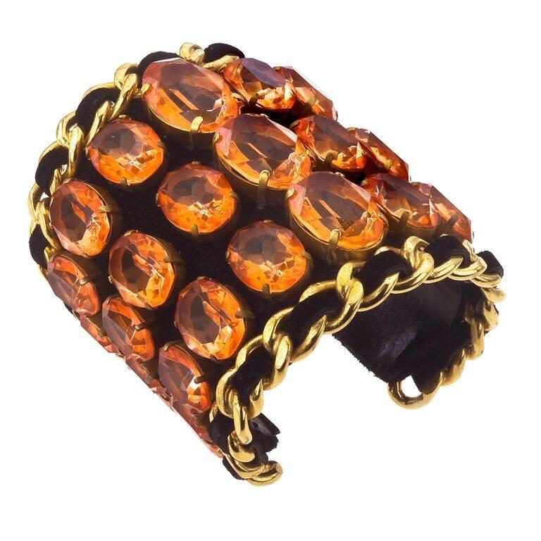 Description: Very important, extremely rare massive Chanel bangle with chain detail and orange rhinestones on black velvet. From 1991 Fall/Winter collection.
