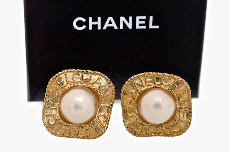 Vintage CHANEL Logo Pearl Concave Earrings  Measurements: Height: 1 3/8 inches Width: 1 3/8 inches  Features: - 100% Authentic CHANEL. - Concave inverted square with CHANEL inscriptions. - Faux pearl centre piece. - Clip back earrings. - Signed