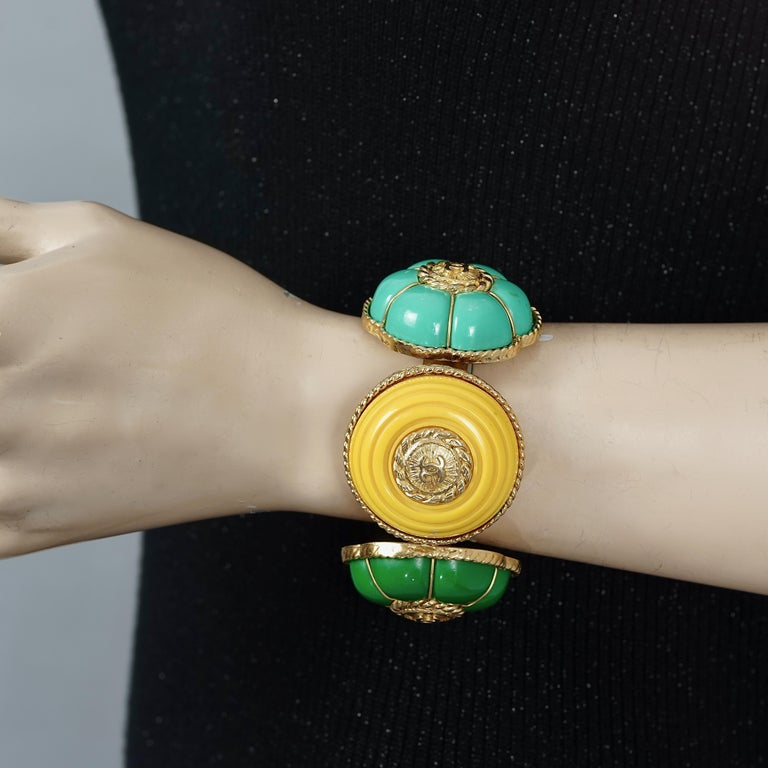Vintage CHANEL Multicolor Logo Buttons Cuff Bracelet  Measurements: Height: 1.65 inches (4.2 cm) Circumference: 6.42 inches (16.3 cm) including the opening  Features: - 100% Authentic CHANEL. - Chanel cuff with 4 colorful resin buttons and metal CC