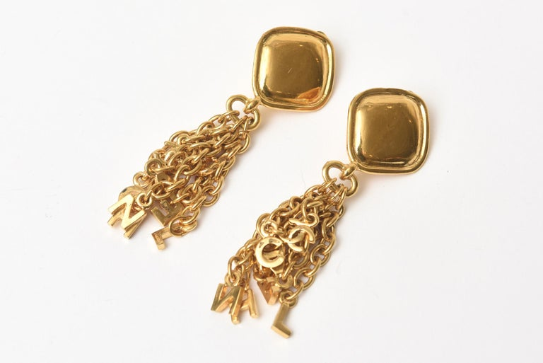 These fun, chic yet sophisticated Chanel clip on dangle earrings have charm like pendants in chain form hanging from the top with CC's. They are gold plated and are dramatic. They are from the 20th century of the 90's. They can go all seasons day to