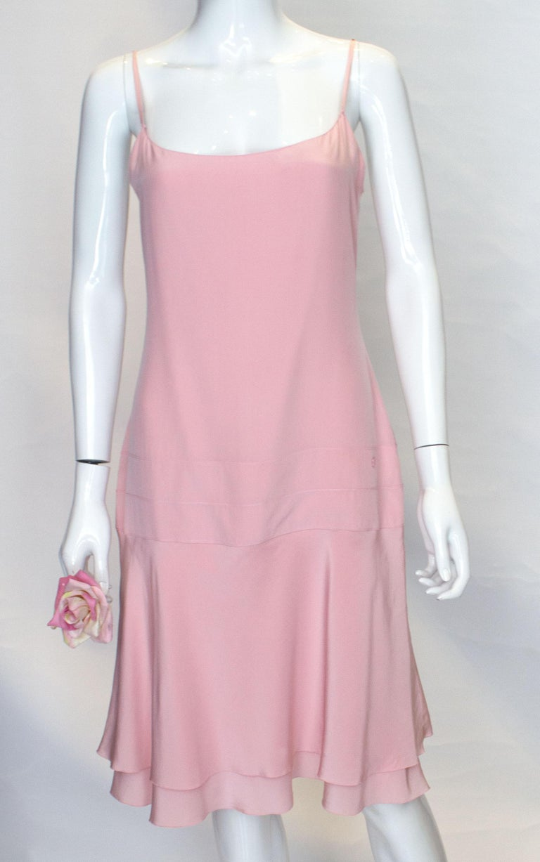 A pretty dress for Summer by Chanel. This dress is easy to wear and the fared hem moves with you as you walk. It is super soft silk on the outside and lining, and has spagetti straps and a central back zip. There is a subtle Chanel detail at hip