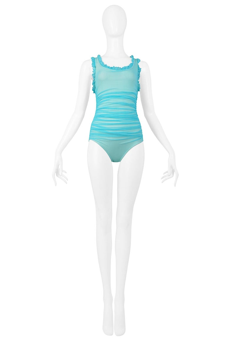 Vintage Chanel turquoise blue mesh racer back one piece swimsuit, featuring a ruffle neckline, ruched side detail, and embroidered Chanel logo patch at center back.  Excellent Vintage Condition.  Size 38
