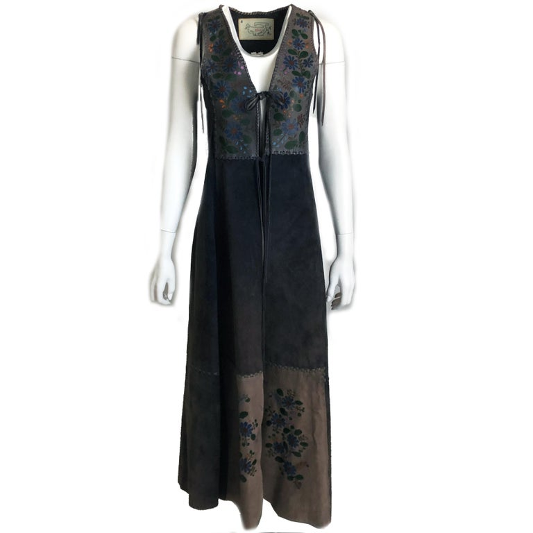 This unusual long festival vest or dress was designed by Char, Charlotte Blankenship de Vasquez, likely in the early 1970s. Made from gray suede leather, it features whip stitching & leather panels with colorful hand painted florals.  Unlined: