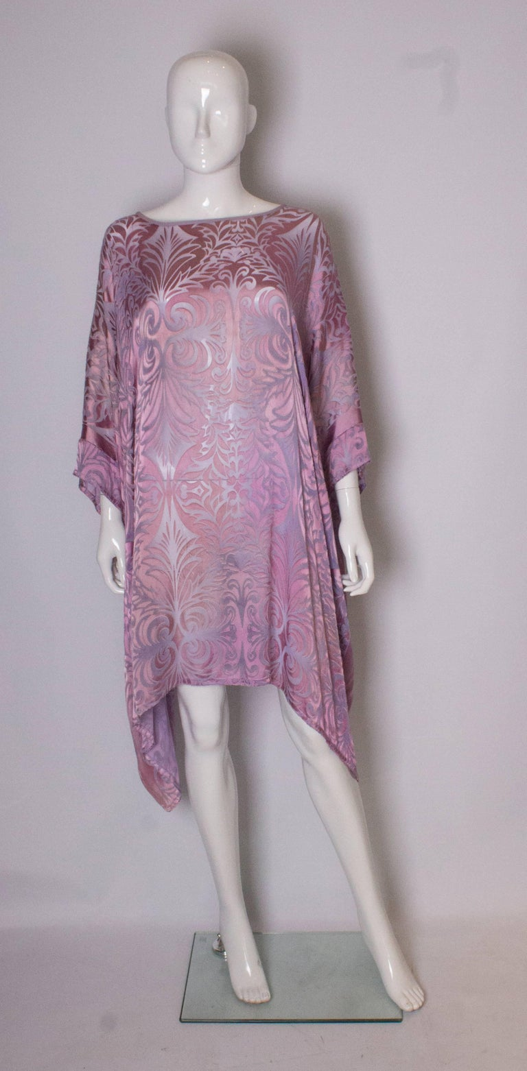 A pretty vintage lilac tunic dress by Charles and Patricia Lester Couture. The dress/tunic is meant to be worn loose, and can fit up to bust 50''. Length 36 ''