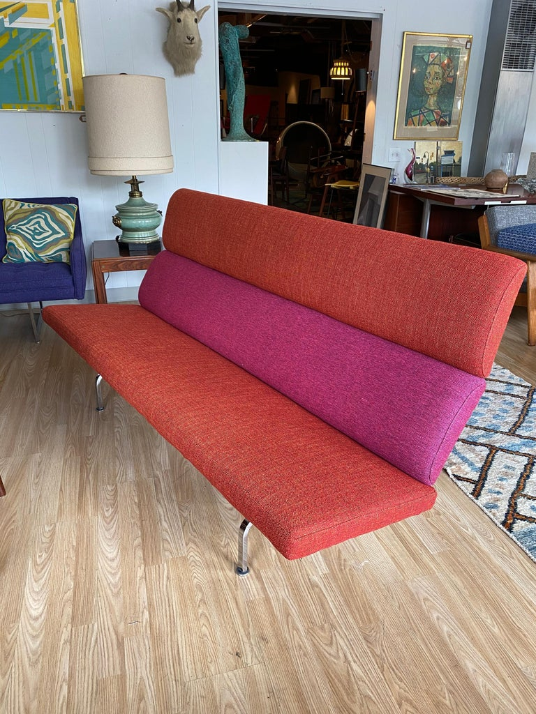 Designed by Charles and Ray Eames for Herman Miller, this bold and bright vintage compact sofa is in overall good condition.  New upholstery in red and pink tweed. Circa 1950s. USA. Dimensions: 28