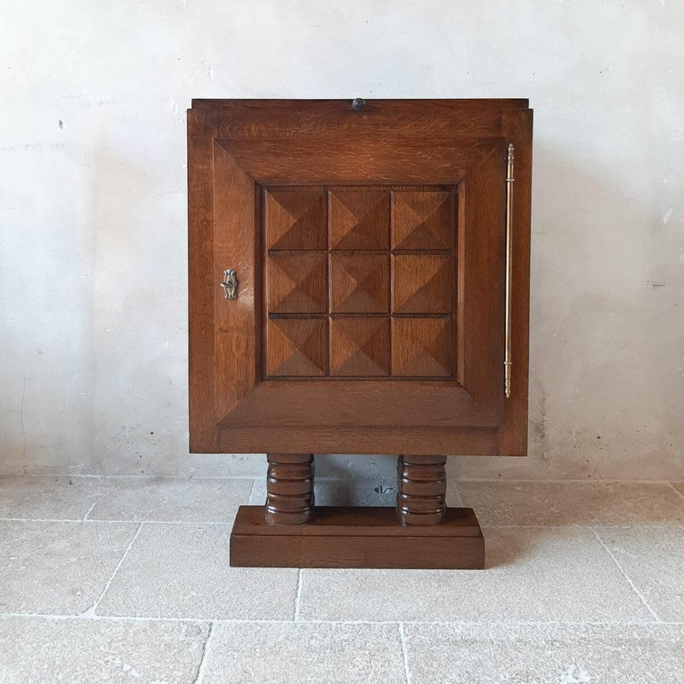 Midcentury vintage Charles Dudouyt wall cabinet. This Brutalist cupboard or bar cabinet in it's original darkened brown oak has geometrical, graphic details on the door, which is a signature relief seen often on Charles Dudouyt work and shows its