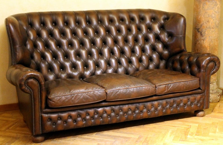 This English vintage brown leather Chesterfield sofa with button trufted back and arms offers three seats and high back, striking profile thanks to slight winged back, scrolled arms and gently scalloped back rail, the all resting on solid turned