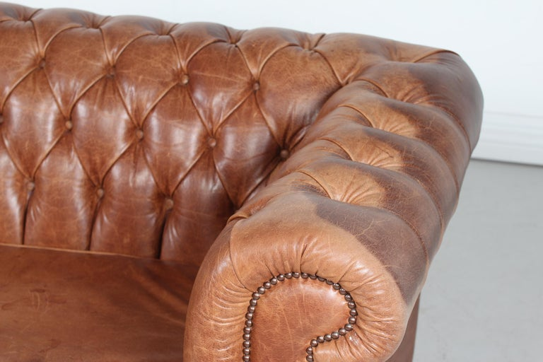 Vintage 3-seat Chesterfield sofa made in the 1970s. It's upholstered with delicate and good quality cognac colored leather with numerous buttons.   Measures: Length 188 cm Height 72 cm Seat height 43 cm Depth 90 cm  The sofa is in good