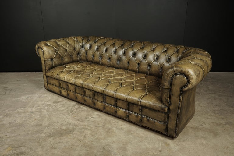 Vintage Chesterfield sofa from England, circa 1950. Original green leather upholstery with buttoned seats. Great wear and patina. Wheels underneath.